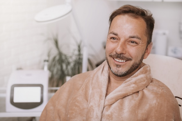 Happy mature man relaxing at spa center