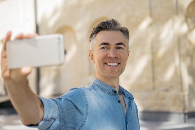 Happy mature man taking selfie using smartphone.