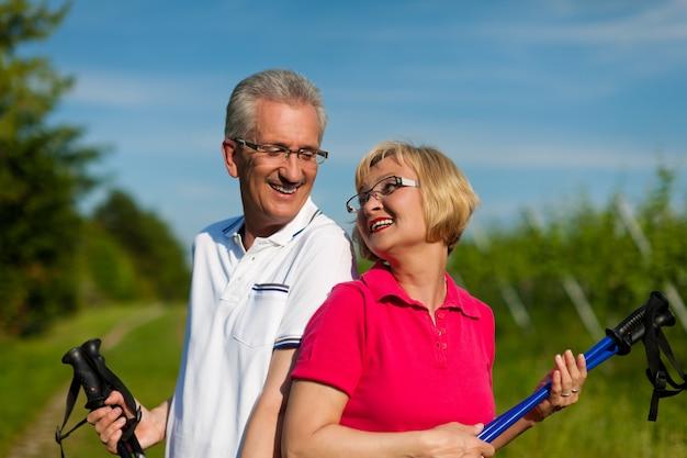 Счастливая зрелая или пожилая пара занимается северной ходьбой летом