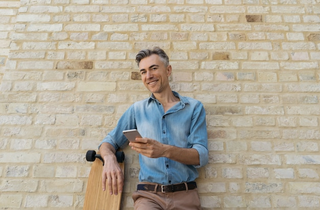 Happy mature skater with longboard, standing near wall, holding smartphone, smiling