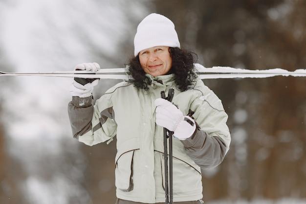 겨울 공원에서 행복한 성숙한 woam. 여가에 숲에서 트레킹하는 레이디 액티브웨어.