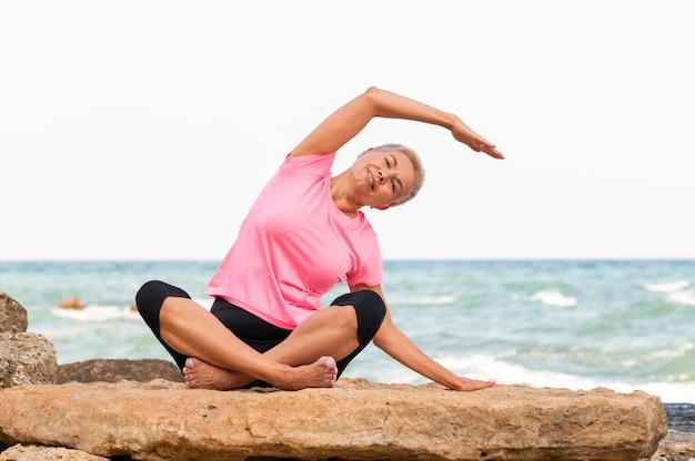 Счастливая зрелая женщина на берегу моря делает упражнения йоги