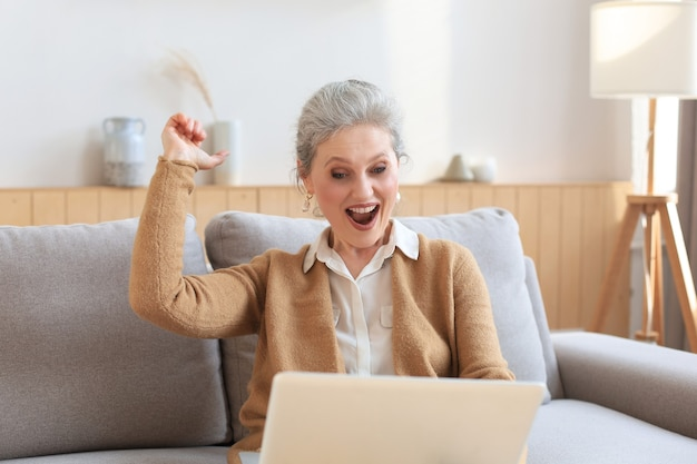 Happy mature woman celebrating online win using laptop sitting on couch at home.