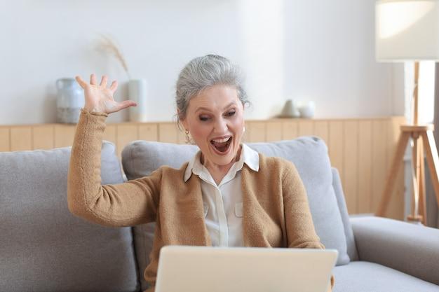 Счастливая зрелая женщина празднует онлайн-победу, используя ноутбук, сидя на диване у себя дома.