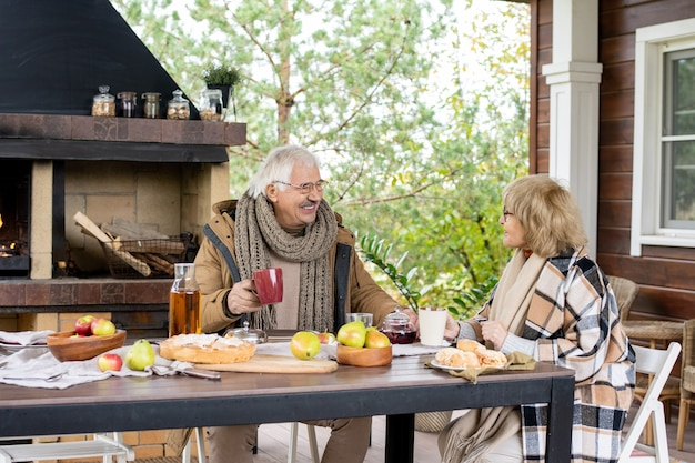 Happy mature woman in eyeglasses and warm casualwear looking at her husband while both having tea with homemade snacks against fireplace