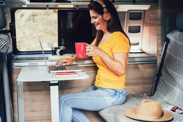 ミニキャンピングカーの中でコンピューターのラップトップを使用して楽しんで幸せな成熟した女性-顔に焦点を当てる