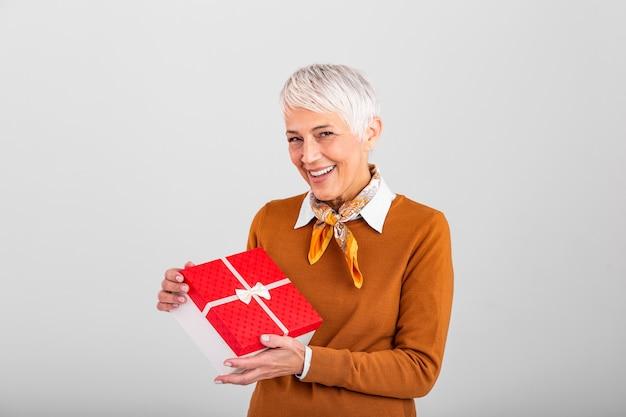ギフトボックスを保持し、クリスマススタイルでそれを見て幸せな成熟した女性