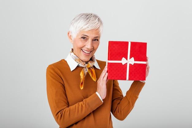 ギフトボックスを保持し、それを見て幸せな成熟した女性