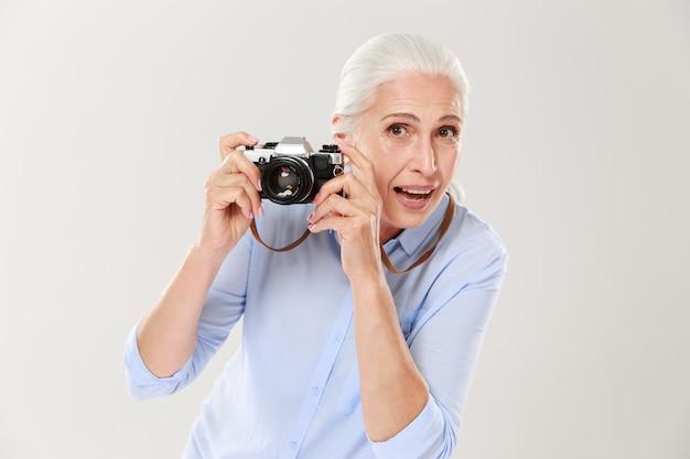 Happy mature woman holding retro camera isolated