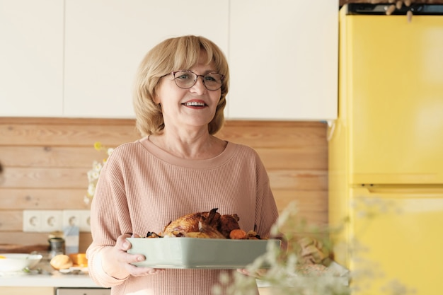 七面鳥と笑顔で皿を保持眼鏡で幸せな成熟した女性