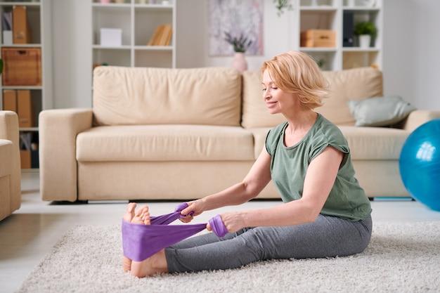 회색 레깅스와 거실 바닥에 앉아 집 검역 중 다리 운동을하는 티셔츠에 행복 한 성숙한 여자