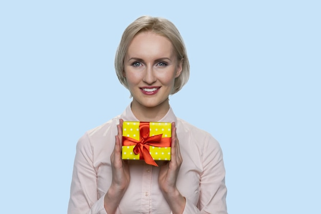 Happy mature woman is holding a gift box