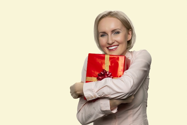 Happy mature woman is hugging a red gift box