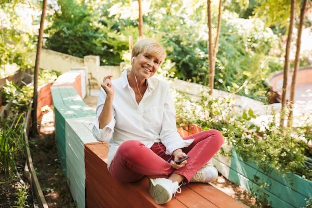 Счастливая зрелая женщина слушает музыку с наушниками