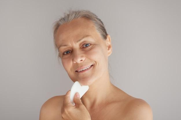행복한 성숙한 여성은 회색 배경에 격리된 옥 판자로 얼굴을 마사지한다