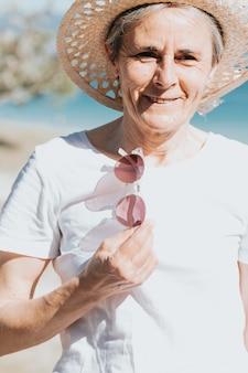 トレンディなサングラスと帽子とビーチで50年の幸せな成熟した女性