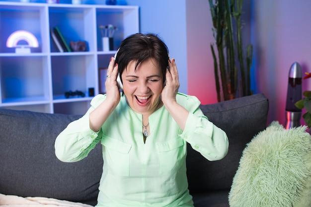 家で踊るヘッドフォンで幸せな成熟した女性。モダンなインテリアでヘッドセットを使用して音楽を聴いて楽しんでいる高齢者の女性。技術、人、ライフスタイルのコンセプト。