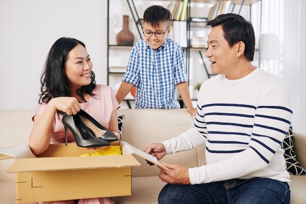 幸せな成熟した女性は彼女の夫と息子から誕生日プレゼントを開き、新しいかかとを取り出します
