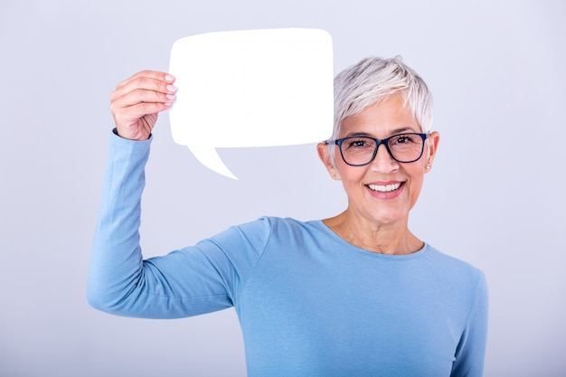 Happy mature woman in plain blue long sleeve t-shirt holding empty speech bubble isolated on wall. woman showing sign speech bubble looking happy