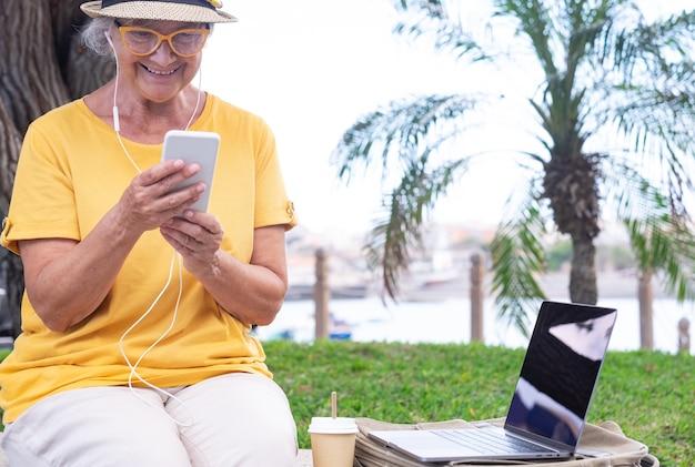 옆에 스마트 폰 노트북 컴퓨터를 사용하여 야외에 앉아 있는 행복한 성숙한 여성
