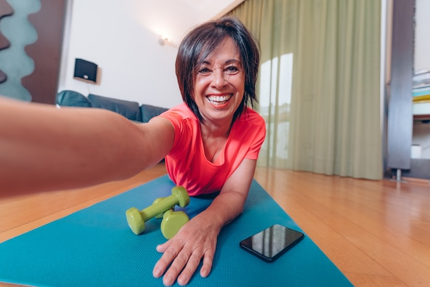 Happy mature woman taking a selfie at workout gym at home
