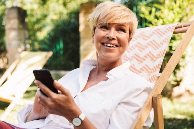 Счастливая зрелая женщина, с помощью мобильного телефона