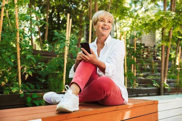 携帯電話を使用して幸せな成熟した女性