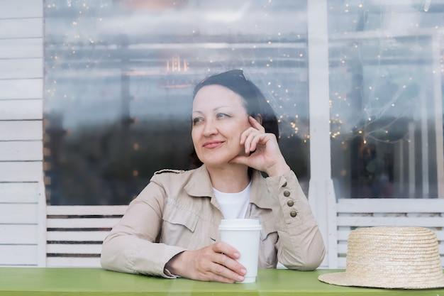 コーヒーを飲みながら幸せな成熟した女性は、カフェの夏のベランダのテーブルに座って微笑んでいます。