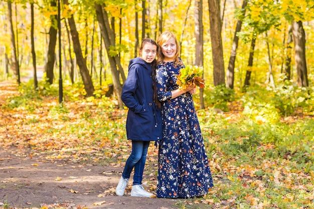 秋の公園で大人の娘と幸せな成熟した女性