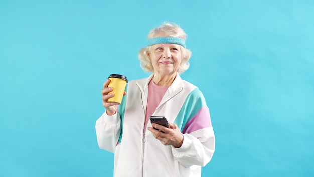 Happy mature woman with gray hair in a tracksuit checks the notification on a modern smartphone.