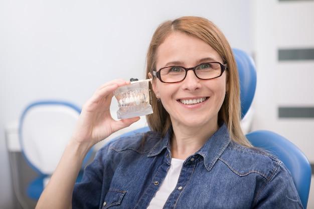 Счастливая зрелая женщина со здоровыми белыми зубами улыбается, держа модель челюсти с брекетами