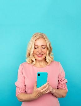 青い壁に隔離された携帯電話で幸せな成熟した女性。