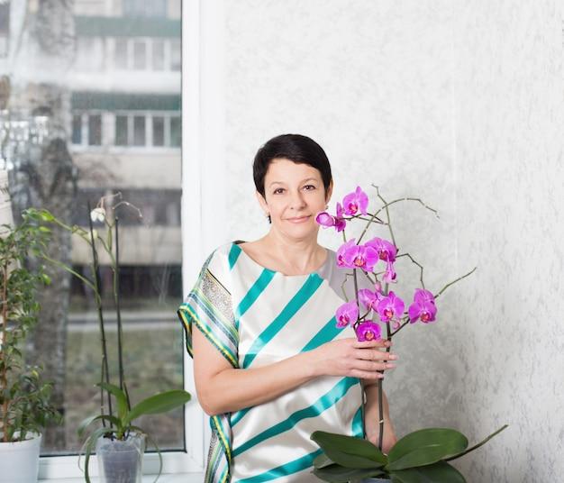 胡蝶蘭の屋内で幸せな成熟した女性