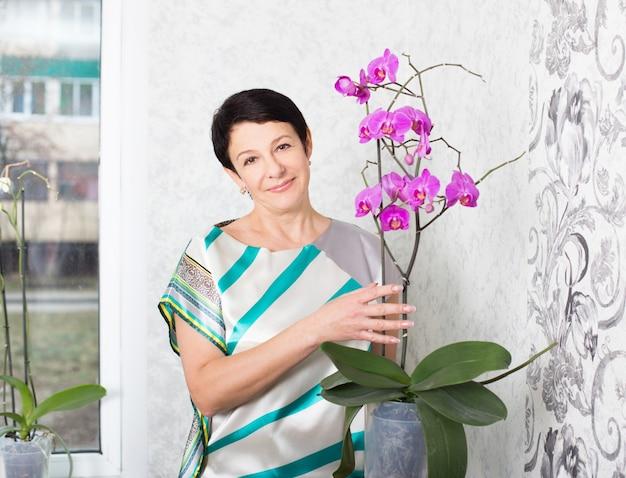 屋内で胡蝶蘭と幸せな成熟した女性