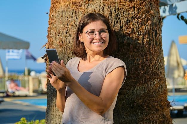 Счастливая зрелая женщина с смартфоном.