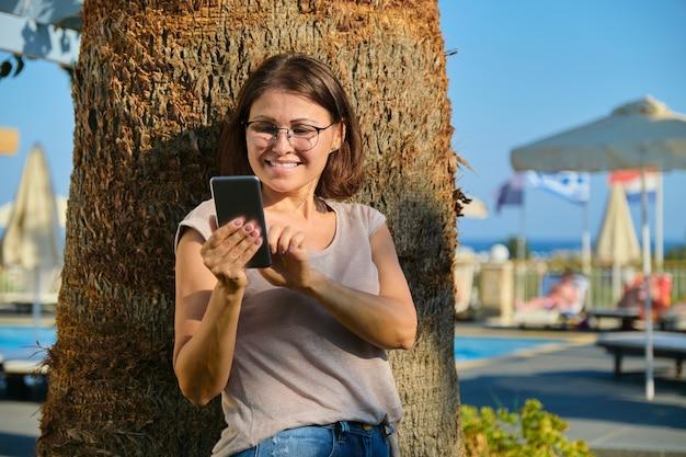 Счастливая зрелая женщина со смартфоном