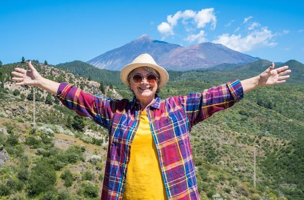 야외에서 하이킹을 즐기고 있는 밀짚 모자를 쓴 행복한 성숙한 여성. 테이데 화산을 배경으로 한 산