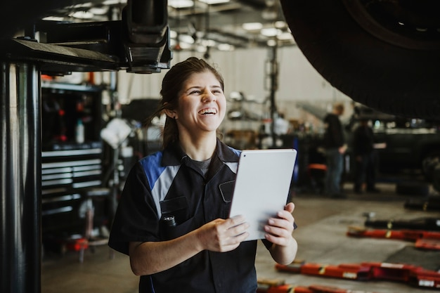Happy mechanic running a diagnostic on a vehicle