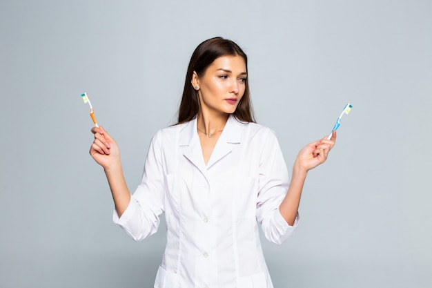 Счастливый врач женщина, держащая зубные щетки, изолированные на белой стене