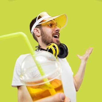 幸せな出会い。シャツを着た若い男のハーフレングスのクローズアップの肖像画。ヘッドフォンと飲み物を持つ男性モデル。人間の感情、表情、夏、週末のコンセプト。