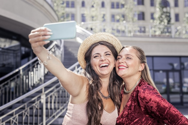 幸せな思い出。一緒に写真を撮りながら笑顔で喜んでポジティブな女性