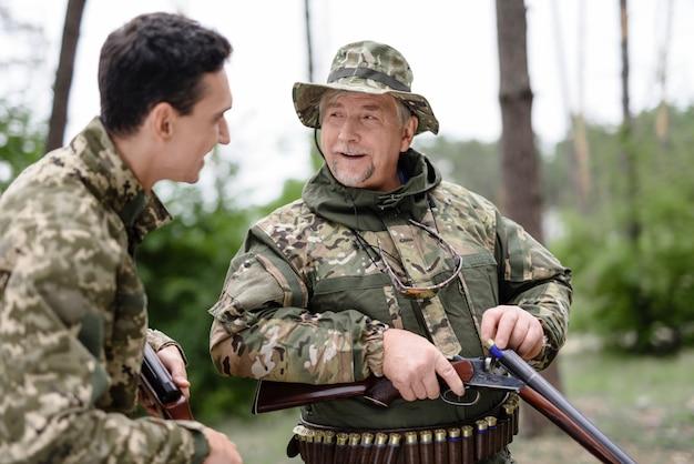 Happy men charging rifle наслаждайтесь сезоном охоты.