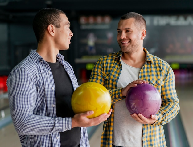 Happy men holding a colorful bowling balls