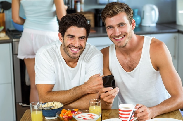 Happy men holding mobile phone while having breakfast at home