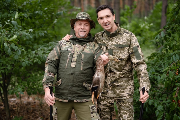 Happy men holding wildfowl and posing for photo.