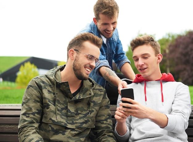 Uomini felici che guardano lo smartphone e si siedono sulla panchina