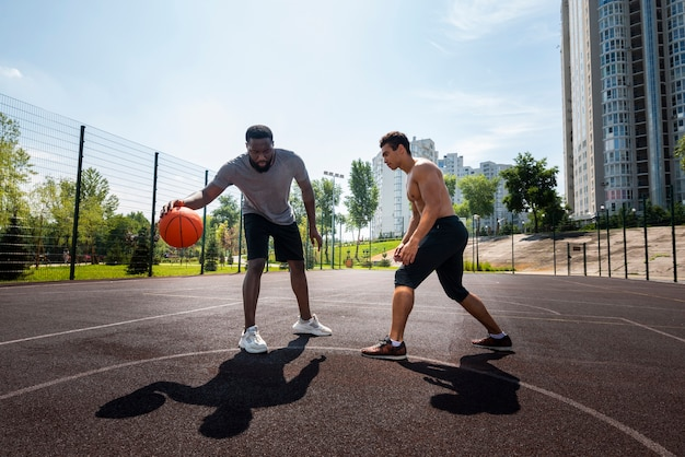 Happy men playing urban basketball long shot
