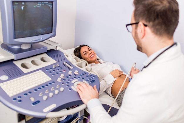 Happy mid adult female patient going through abdomen ultrasound at clinic