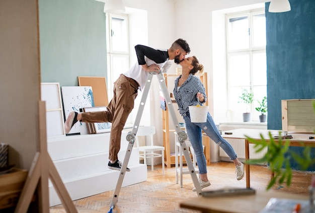 Happy mid adults couple kissing when painting indoors at home, relocation and diy concept.