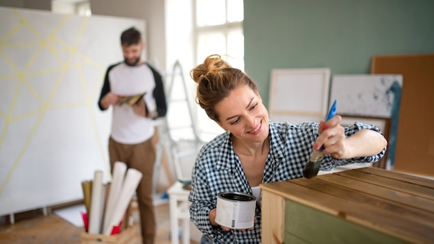 Happy mid adults couple painting furniture indoors at home, relocation and diy concept.